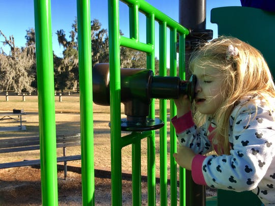 Avery Guidry, 3, looks through a toy telescope attached