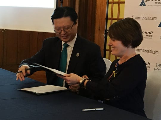 Wonroe Lee of JGBLI and Niki Hinckle of Summit Health exchange copies of an agreement during a signing ceremony on Jan. 18, 2018, at the former Fort Ritchie, Maryland.