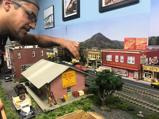 David Todd Magill adds some details to the train display in the basement of his Selkirk home.