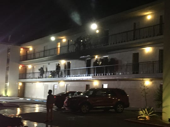 Palm Springs firefighters check rooms at The Roadway Inn Friday evening after a fire forced guests to evacuate and damaged several rooms.