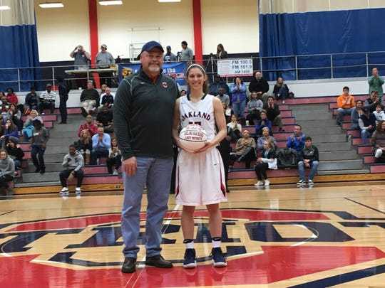 Oakland senior Sloan Mann poses with OHS principal Bill Spurlock after Mann was honored with a basketball for surpassing 1,600 points in her career.