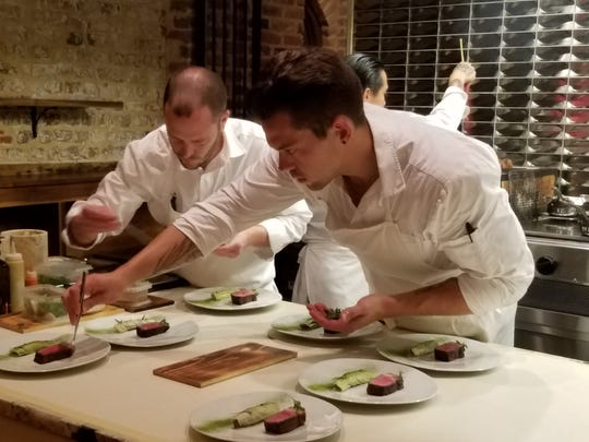 Kitchen staff at McCrady's in Charleston, S.C., carefully plates dishes that are part of a new tasting menu.