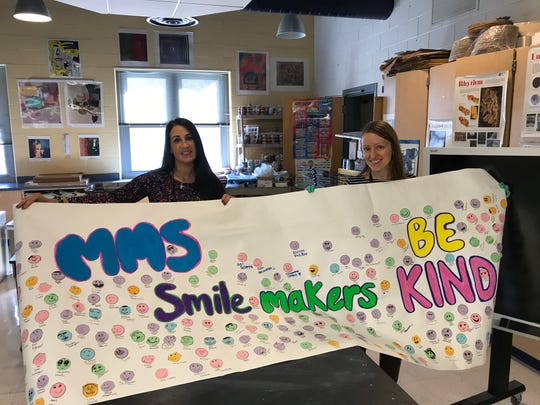 Character Education teacher Lia Caravella, left, and art teacher Amanda Hatzikyriakou display students' signed 'Be Kind' banner at Cedar Grove Memorial Middle School.