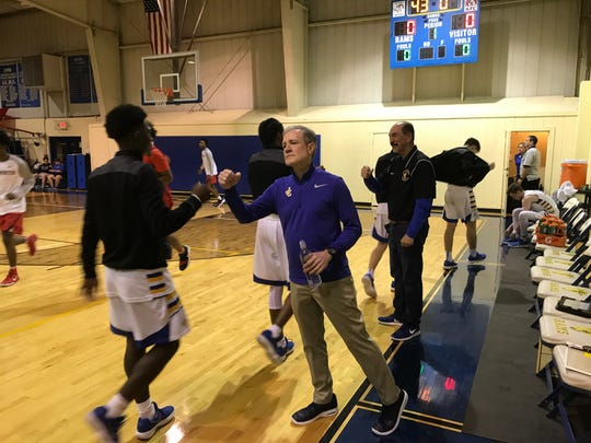 John Carroll Catholic assistant coach Mark Rodgers (right) fist bumps junior guard Vontravious Sands before playing Westminster Academy on Tuesday, Jan. 23, 2018 in Fort Pierce.