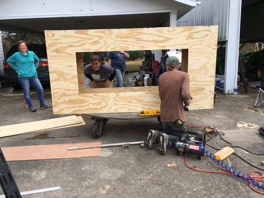 Krewe members put the finishing touches on a walking float that will be used in the Krewe de Canailles parade.