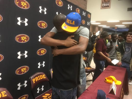 Mountain Pointe's Kenny Churchwell hugs his family after donning a UCLA hat announcing his college choice on Friday, Jan. 26, 2018.