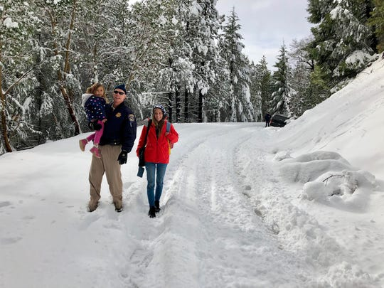 Officer Chad Millward holds 3-year-old Cinnamon Cordova as the girl's mother, Amanda Cordova, looks on. The Cordova family was rescued by a CHP helicopter after their truck got stuck on a snow-packed road in Trinity County.