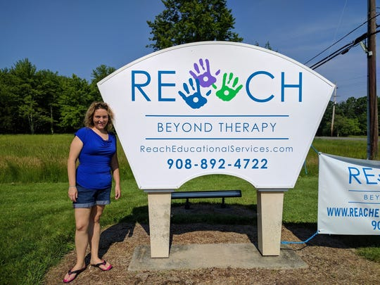 Founder Stefanie Reuters-Hutchins stands next to the Reach Education Services sign before an open house last summer.
