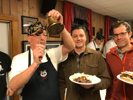 American Legion Post Adjutant Mark Corgiat (left) rings the bell for first time raccoon eaters Rick Gray (middle) and Jason Hoffe during the 92nd annual Coon Feed in Delafield. This year's event is Saturday, Jan. 26.