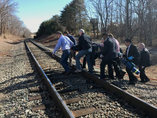Sen. Bill Cassidy, R-La., (second to the right) helps others transport an injured person after a train crash in Virginia.
