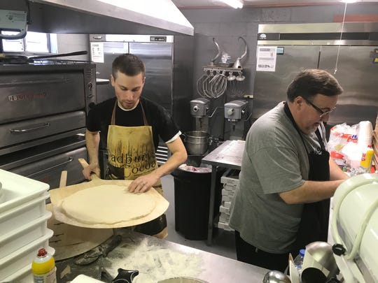 Michael Minto, left, and his father, Marty Minto, work together in the kitchen at Mama Minto's Pizzeria in Iva.