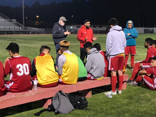 Hueneme High coach Tuck Engelmann (top) addresses his team at halftime of the Vikings' 1-1 tie at Oxnard High on Thursday.