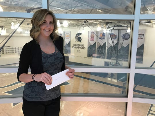 """Inside the Breslin Center offices Thursday night, Michigan State graduate, Kelli DeVlieger, drops off a letter she wrote to Spartans head basketball coach, Tom Izzo. She ended her letter with a message of encouragement. """"Stay strong, coach. We love you."""""""