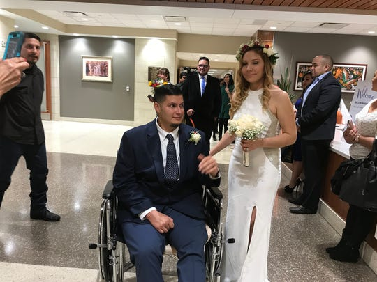 Robert Valdez, who is recovering from a massive stroke, took a break in his wheelchair after marrying his bride Thursday.
