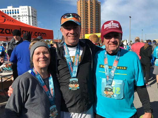 Barbara Partrick, 70, and Howard Partrick, 71, are joined by their son, Glenn (center) after all three Tate High graduates completed the Pensacola Double Bridge Run. Howard and Barbara trained since October to participate for the first time.