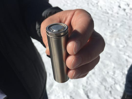 Tesla co-founder J.B. Straubel holds an example of the battery cells the company manufactures alongside Panasonic in the Tesla Gigafactory in Nevada. Straubel had the cell at an event at Squaw Valley Resort on Feb. 5, 2018.