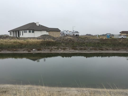 Construction of homes continues along Oso Creek — some close enough that their roofs are reflected in the water.