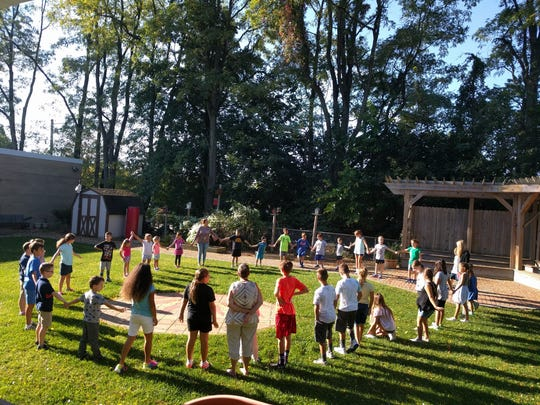 Kindergarten students at Denville's Riverview Elementary School hold a morning meeting in the sun.