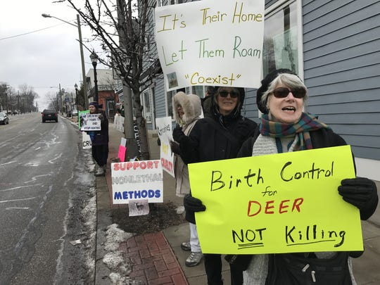 Activists Dianne Hoffman and Zorina Weber carry banners during the Animal Protection League of New Jersey and League of Humane Voters' protest in Verona, in response the Essex County Deer Management Program.