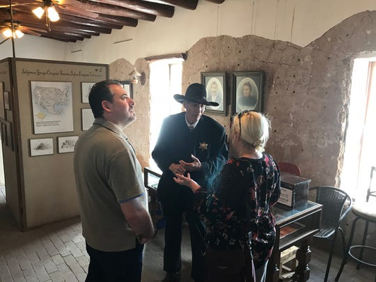 The sheriff, played by Manny Alvarado of the El Paso Pistoleros, talks with visitors Saturday at the old El Paso County jail in San Elizario. The town is having a two-day art festival for Valentine's Day.