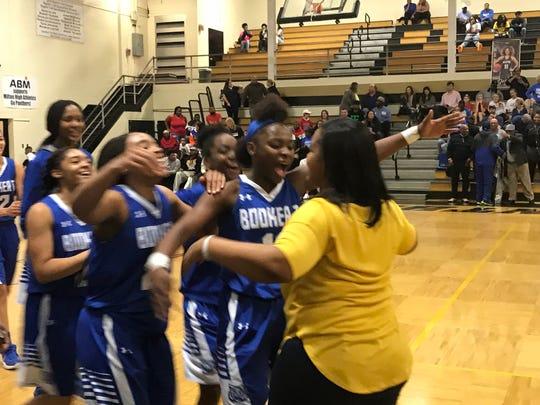 Booker T. Washington coach Jade Brown embraces her players after the Wildcats beat Pensacola High in the District 1-7A girls basketball tournament title game.