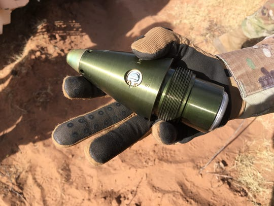 A soldier holds a fuse for an artillery round.