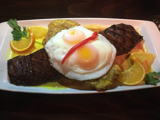 A Cuban take on steak and eggs features grilled skirt steak topped with two eggs, sunny-side up, and a side of tostones, or fried plantains.