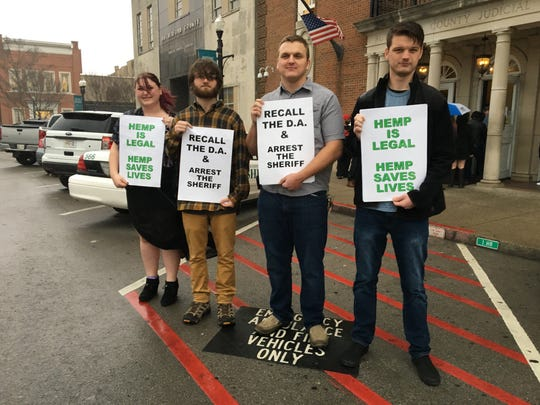 Standing in a downpour are protesting the arrest of shop owners accused of selling CBD oil are, from left, Julia Beasley, Luke Sabin, Logan Weaver and Tyler Bailey. All four use CBD oil in their electronic cigarettes to help relieve pain from a variety of health issues.