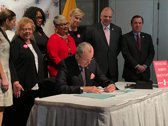 Gov. Phil Murphy, surrounded by lawmakers and advocates in the Trenton War Memorial on Wednesday, Feb. 21, 2018, signs into law a bill providing $7.5 million in state funding for family planning services.