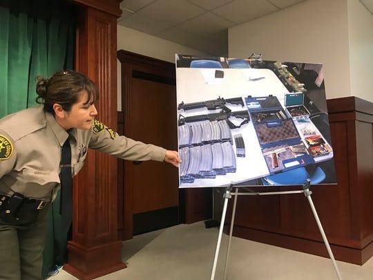 Deputy Lisa Jansen displays photos of weapons and ammunition