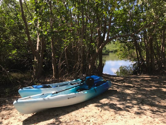 Kayaks are parked in the sand near the beach access at St. Lucie Inlet Preserve State Park.