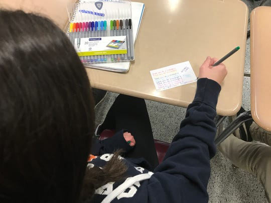A student works on a colorful message of hope to send