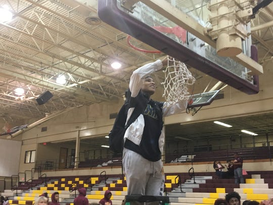 NCHS senior Jolie Williams cuts down the net after