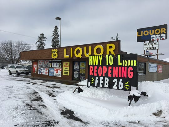 A sign promotes the reopening of Highway 10 Liquor.