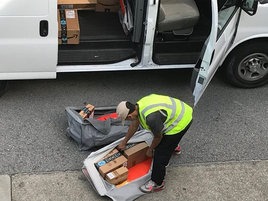An Amazon Logistics driver organizing the day's packages for more streamlined delivery. Amazon Logistics contracts with small and medium-sized delivery businesses nationwide to deliver Amazon packages.