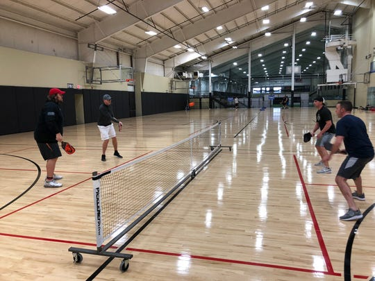 Mark Tauscher, left, in red hat, plays pickleball at 5:30 a.m. with his friends in games that tend to get very competitive.