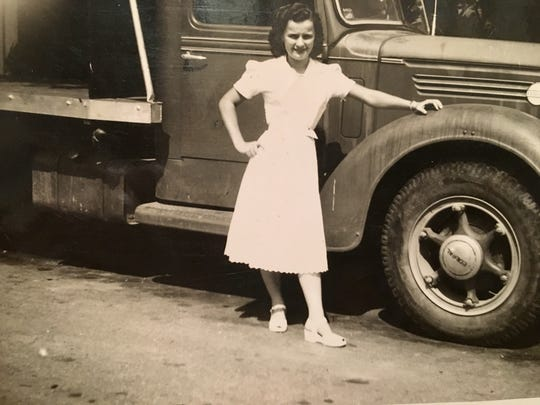 Helen Harney, then a young woman, stands in front of a large farm truck.