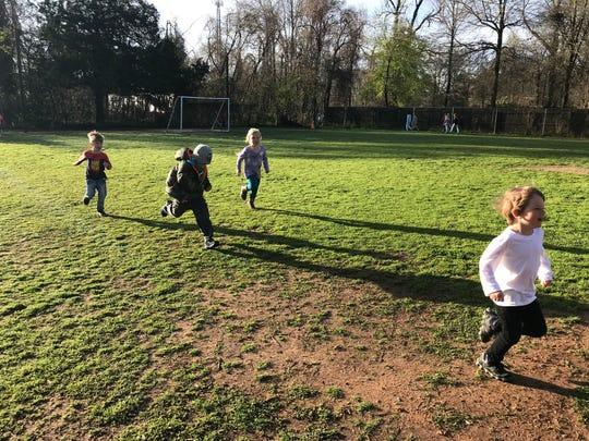 Montessori Educational Center students run laps before school Tuesday morning.