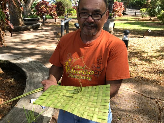 "Chamoru language teacher and weaver Joe ""Dagu"" Babauta shows a dining table mat he wove using coconut leaves or fronds. Babauta said teaching weaving also is an opportunity to teach the Chamoru language."