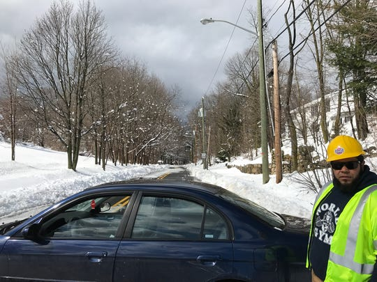 A utility worker blocks off one end of West Ramapo Road in Mahwah. He said many power lines were down and the road was closed for safety purposes.