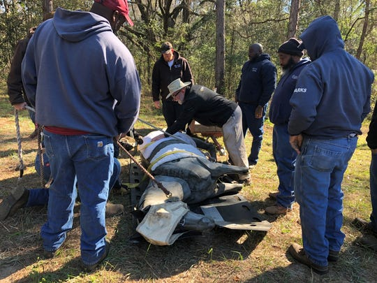 Roger Lauze (white hat) helps volunteers secure a 600-pound dummy horse to a glide at a rescue practice Thursday morning for the Red Hills Horse Trials.