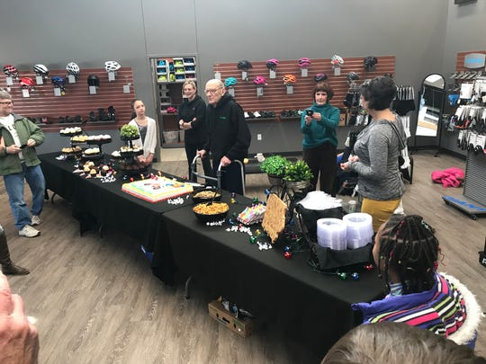 John Karras, co-founder of RAGBRAI, addresses the crowd behind a lavish table full of goodies at his 88th birthday at Bike World in West Des Moines.