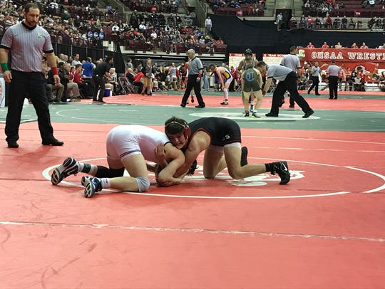 Pleasant senior Carter Wolf, right, holds onto Buckeye