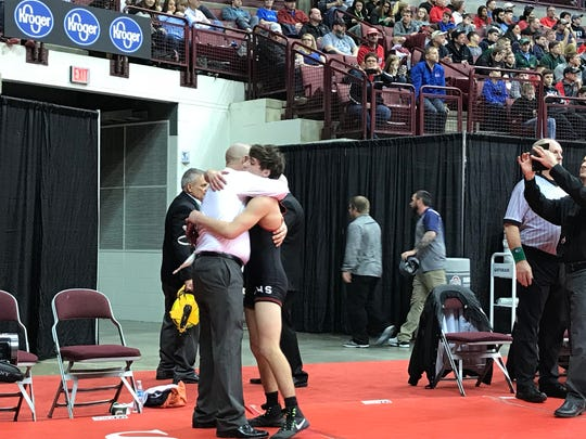 Pleasant senior Carter Wolf and his dad hug following