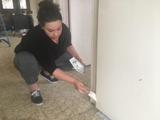 Jeanette Daniels of Twentynine Palms paints a bedroom door in the house being purchased for a Joshua Tree family separated after law enforcement found them living in squalid conditions. Daniels was one of many who volunteered on Saturday, March 10, 2018, to clean the house and get it ready for the family to occupy.