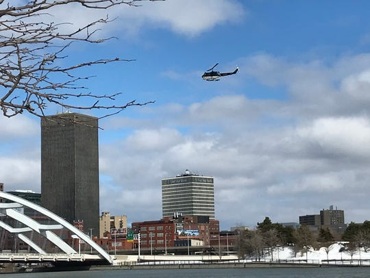 A helicopter searching over the Genesee river Sunday,