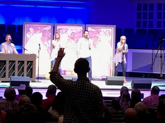 Wesley McCall raises his hand in worship during service at Englewood Baptist Church last summer shortly after diagnosis that his brain tumor was growing again.