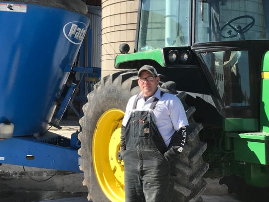 Andy Fisher stands with a tractor he uses on his Reedsville