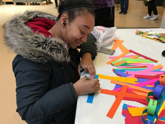 Anastasia Jeans, a senior at Greenfield High School, adds her thoughts to the unity chain on National School Walkout Day on March 14.