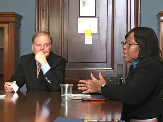 Sen. Doug Jones, D-Ala., talks Thursday to Sheila Tyson, a Birmingham City Councilwoman, and other women attending the Black Women's Roundtable conference.  Black women are credited with helping Jones win his race last year.
